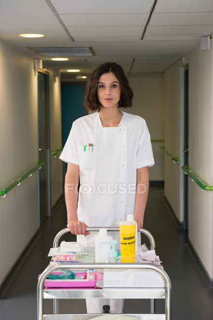 Portrait of female nurse with serving trolley in hospital corridor — Stock Photo