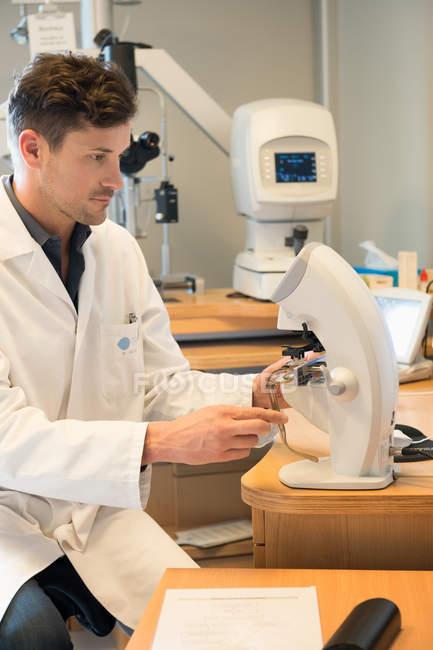 Мужской оптометрист изучает оборудование для тестирования глаз — стоковое фото