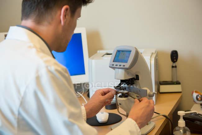 Optometrista masculino examinando el equipo de prueba ocular - foto de stock