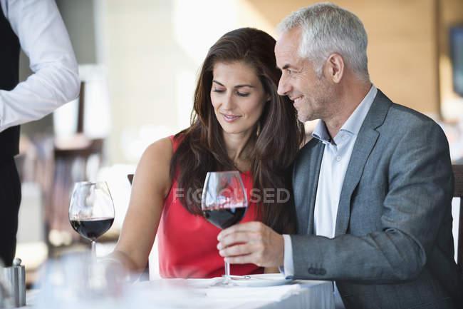 Coppia che si gode il vino rosso nel ristorante — Foto stock