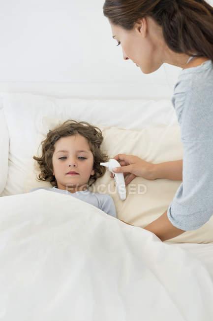 Mujer revisando fiebre de hijo con termómetro - foto de stock