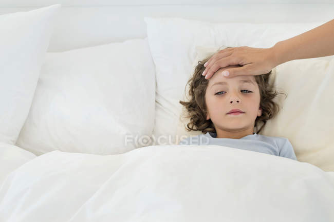 Human hand examining fever of little boy lying in bed — Stock Photo