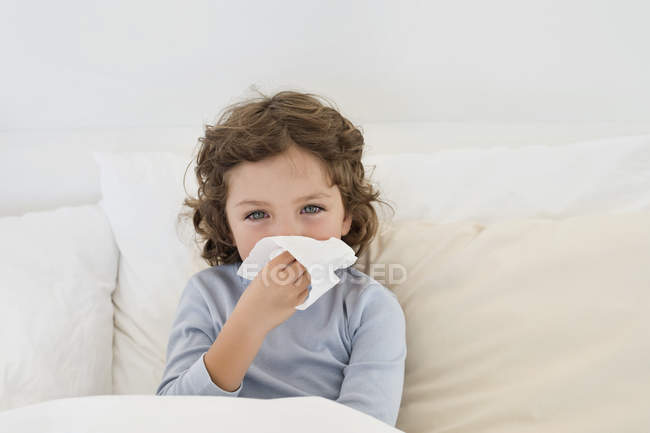 Cute little boy suffering from cold in bed — Stock Photo