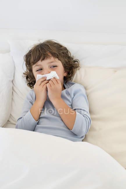 Милий маленький хлопчик страждає від холоду в ліжку — стокове фото