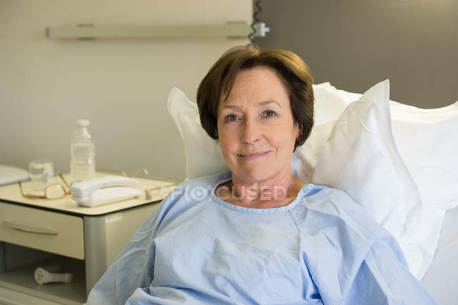 Smiling mature woman lying in hospital bed and looking at camera — Stock Photo