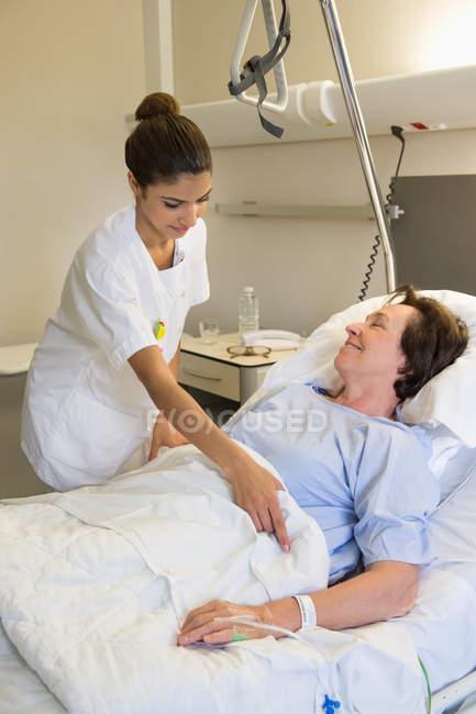 Weibliche Krankenschwester, die Patientin auf dem Krankenhausbett besucht — Stockfoto