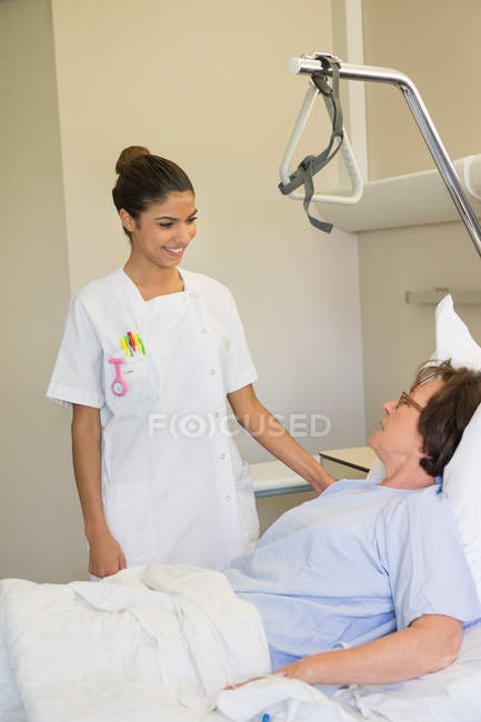 Female nurse attending patient on hospital bed — Stock Photo