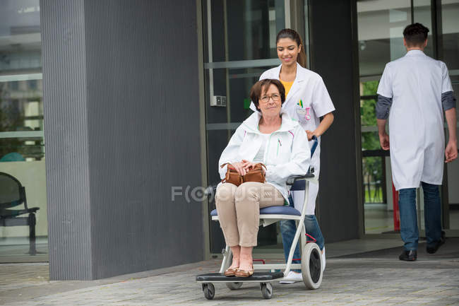 Female doctor pushing patient sitting in a chair — Stock Photo