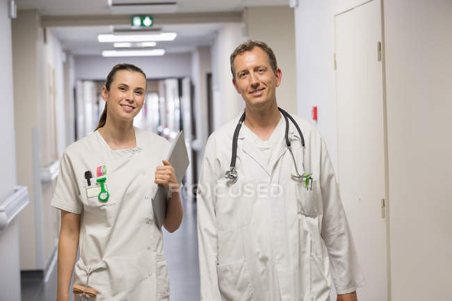 Doctor and female nurse smiling while walking in corridor of hospital — Stock Photo