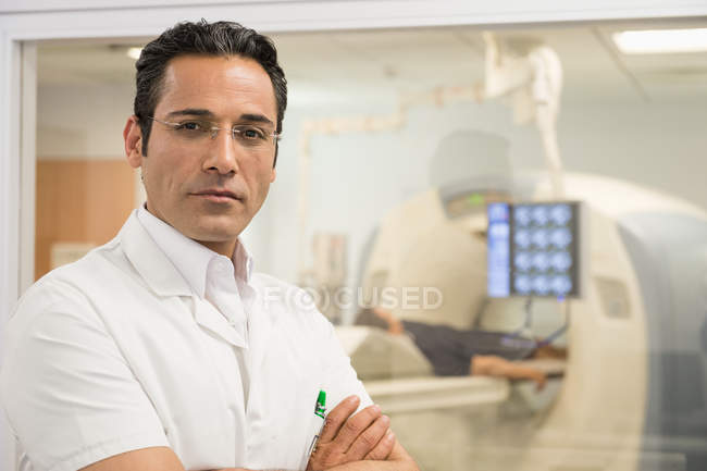 Portrait of smiling male doctor standing in medical MRI scan room — Stock Photo