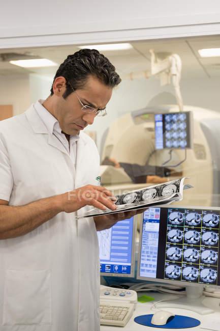 Médico masculino examinando el informe de mri scan en la sala de exploración médica - foto de stock