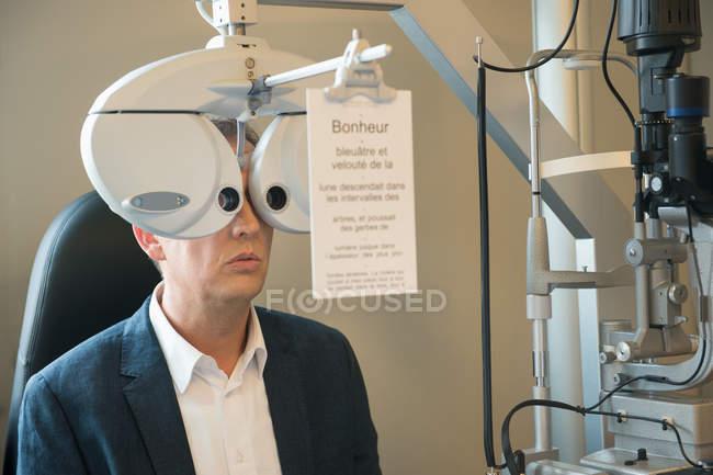 Мужчина пациента, имея офтальмологическое обследование в клинике — стоковое фото