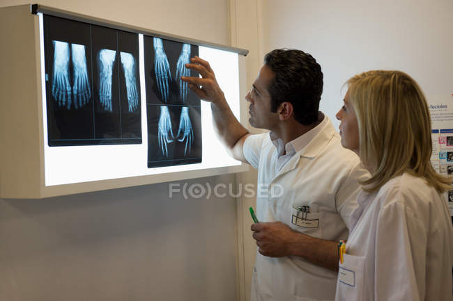 Doctors examining X-ray report in hospital — Stock Photo