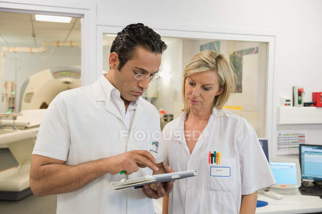 Doctors examining MRI scan report in medical scan room — Stock Photo