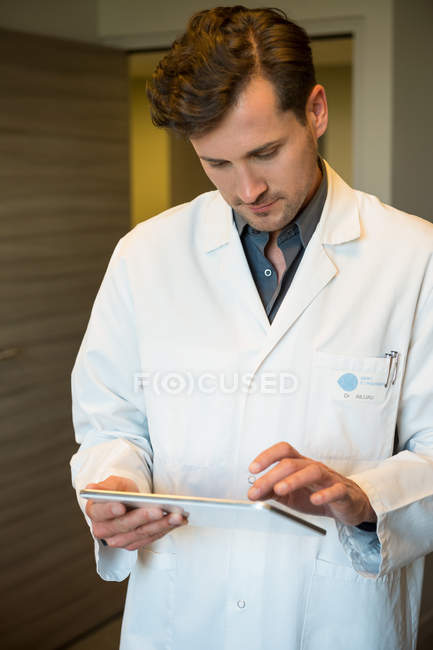 Maschio dottore using digital tablet in clinica — Foto stock