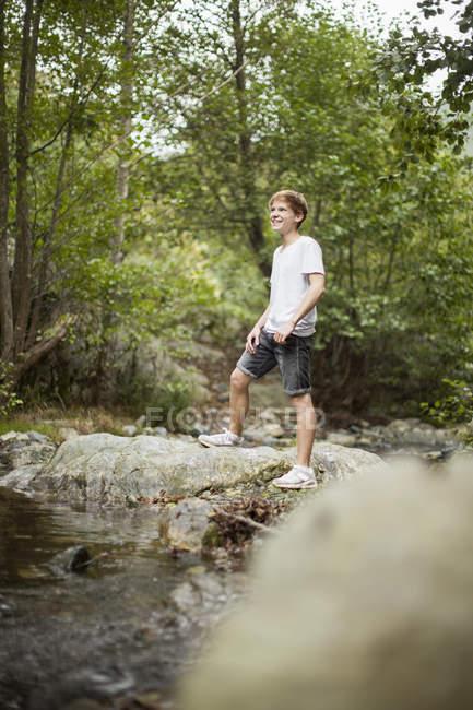 Усміхнений хлопчик, що стоїть у парку — стокове фото