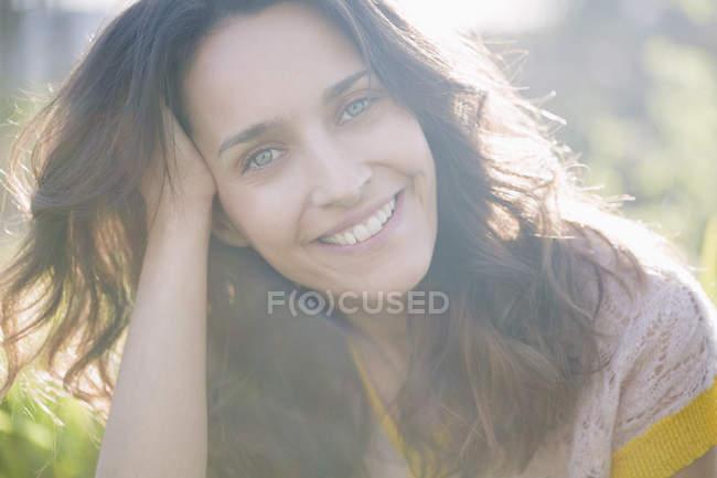 Sonriente mujer en la naturaleza soleada sosteniendo pequeña flor de margarita - foto de stock