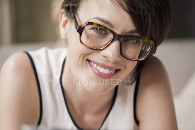 Portrait of smiling woman in eyeglasses looking at camera — Stock Photo