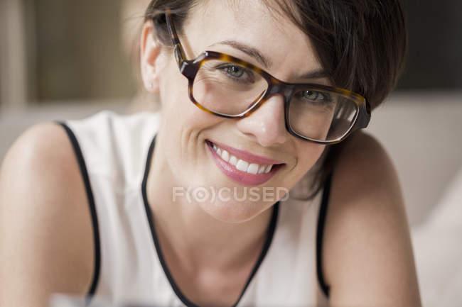 Porträt einer lächelnden Frau mit Brille, die in die Kamera blickt — Stockfoto