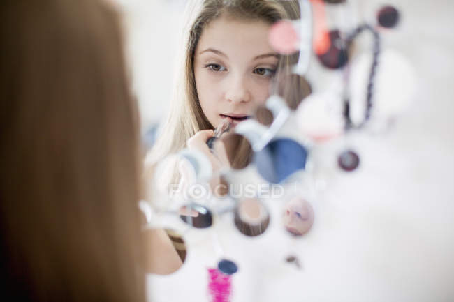 Close-up of teenage girl applying lipstick in front of mirror — Stock Photo