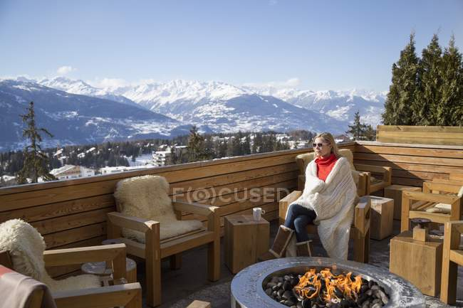 Mujer sentada cerca de hoguera en la terraza del hotel, Crans-Montana, Alpes suizos, Suiza - foto de stock