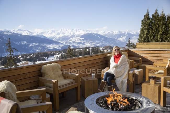 Frau sitzt neben Feuerstelle auf Hotelterrasse, crans-montana, Schweizer Alpen, Schweiz — Stockfoto