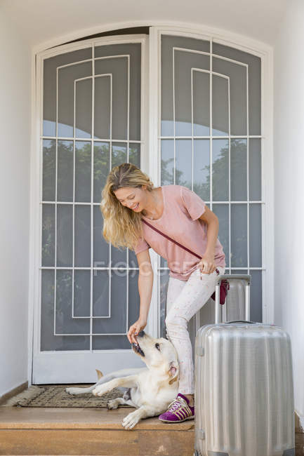 Happy woman with luggage playing with dog at doorway of house — Stock Photo