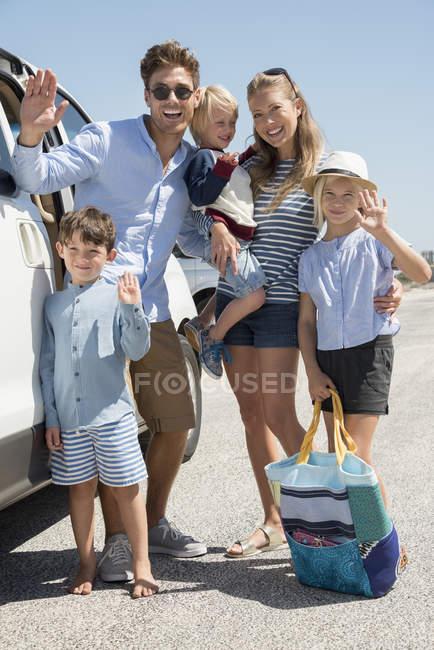 Glückliche junge Familie steht im Urlaub am Auto — Stockfoto