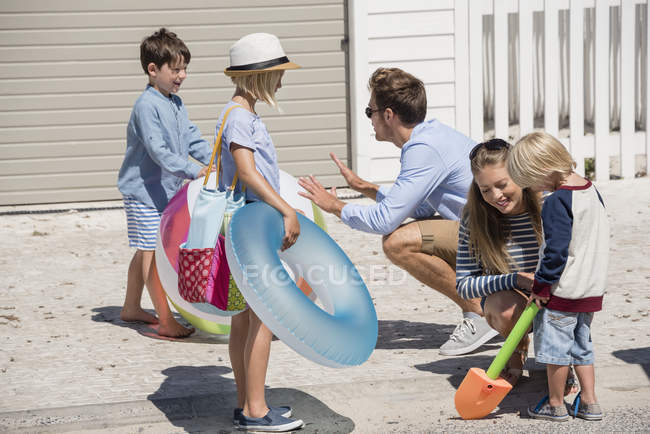 Happy young family with beach gears for vacations — Stock Photo
