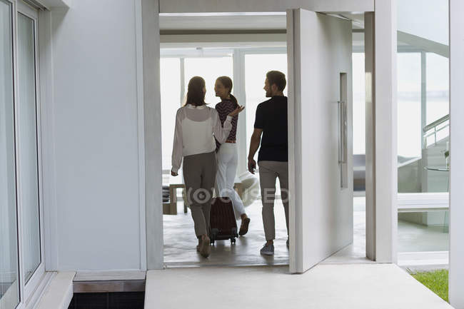Couple with suitcase entering to friend house — Stock Photo