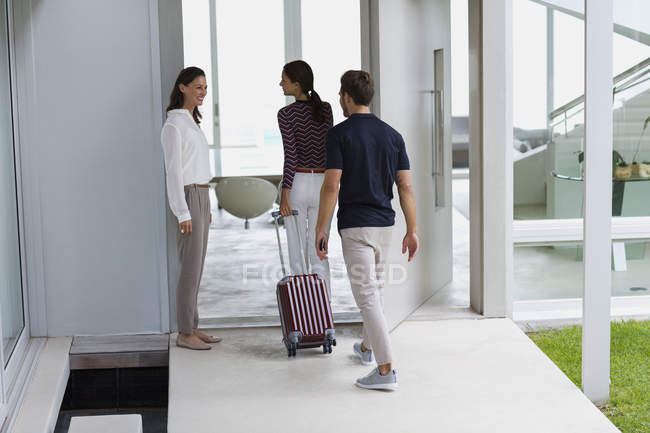 Happy woman welcoming friends with suitcase at doorway — Stock Photo