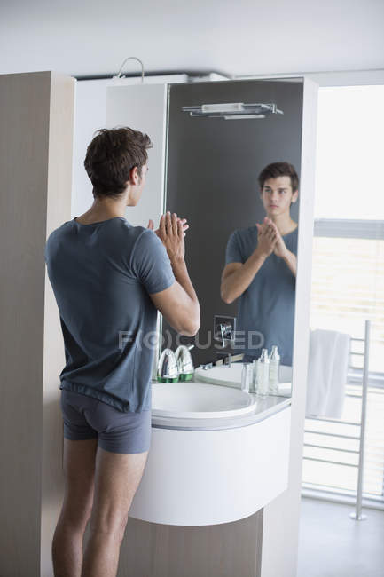 Reflection Of Man Looking At Bathroom Mirror Stock Photo
