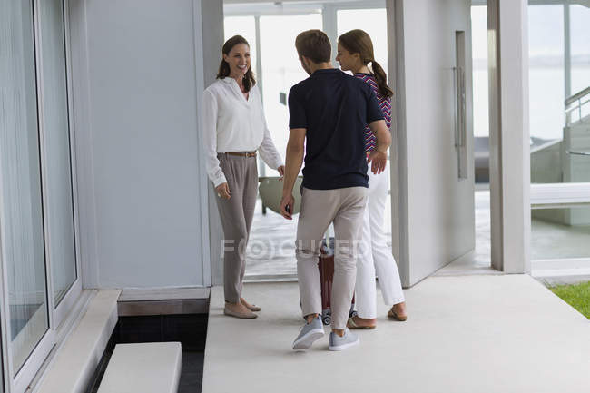 Happy woman welcoming friends at doorway — Stock Photo