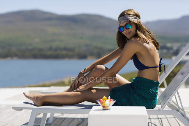 Stylish happy young woman sitting on lounge chair at lake in mountains — Stock Photo