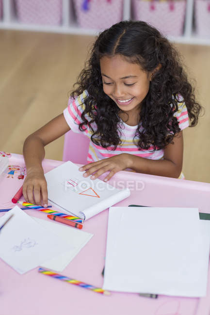 Smiling little girl doing homework at pink table — Stock Photo