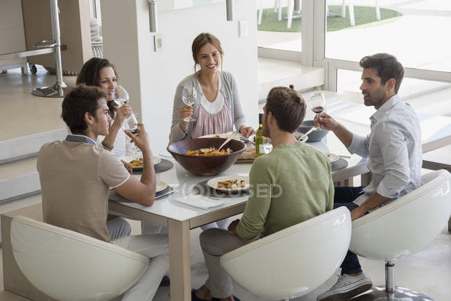 Group of happy friends having lunch at dining table — Stock Photo