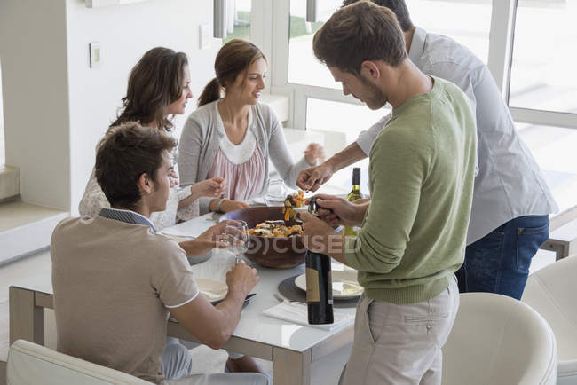 Happy friends having meal at dining table — Stock Photo
