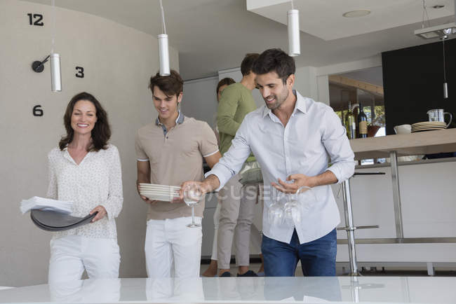 Happy friends carrying dishes for lunch at home — Stock Photo