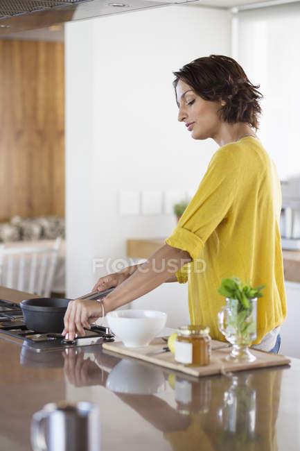 Усміхається жінка готує трав'яний чай кухні — стокове фото