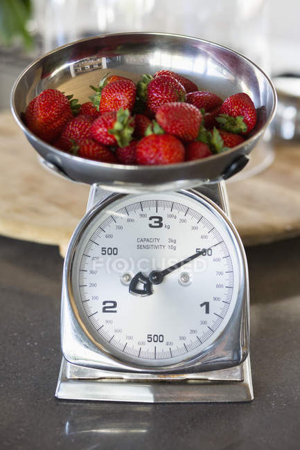 Fresh red strawberries on weighing scale at a kitchen counter — Stock Photo