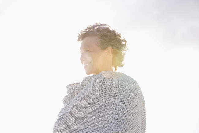 Крупный план зрелой женщины, завернутой в шаль, улыбающейся на открытом воздухе — стоковое фото