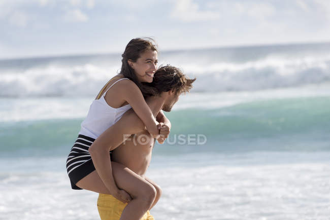 Happy young woman riding piggyback on friend shoulder — Stock Photo
