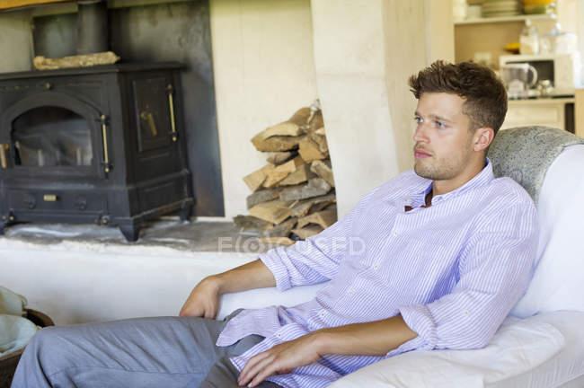 Розслабленої молода людина сидить у крісло і мислення — стокове фото
