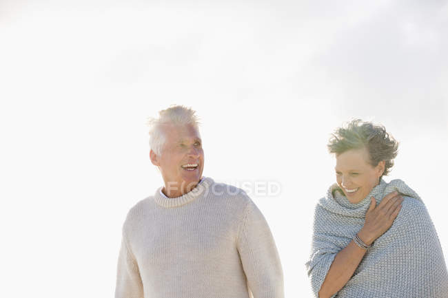 Close-up of laughing senior couple walking together outdoors — Stock Photo