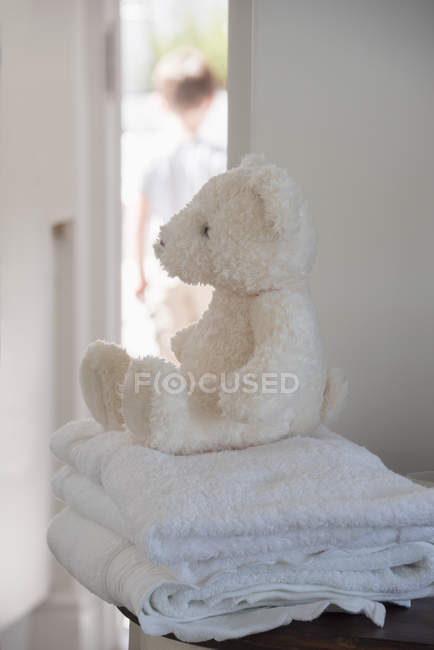 Close-up of soft toy on towels with child in background — Stock Photo
