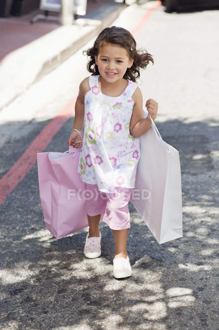 Cute little girl walking with shopping bags on street — Stock Photo