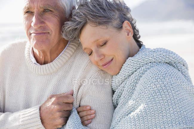 Пожилая женщина отдыхает на плече мужа на пляже — стоковое фото