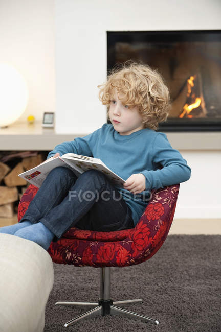 Boy reading a book in armchair in living room at home — Stock Photo