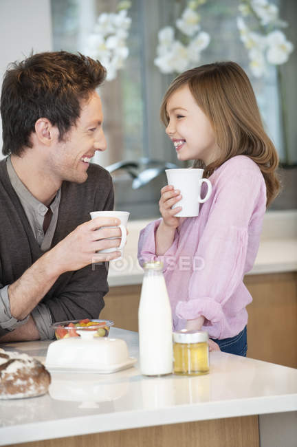 Man drinking tea with happy daughter in kitchen — Foto stock