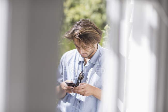 Молодой человек текстовых сообщений со смартфоном на открытом воздухе — стоковое фото
